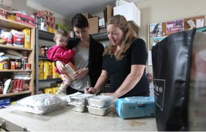 Caitlin Rohde, left, with her one-year-old daughter Violet, helps Made By Momma president Allyson Palaschuk bag up some pre-made dinners. Rohde is a mother of two who delivers diapers, food and other essentials to local client moms a couple times a week.